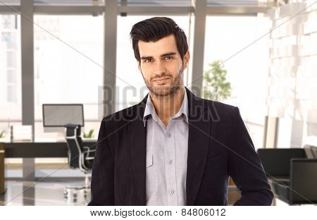 Portrait of goodlooking young businessman at office, smiling.