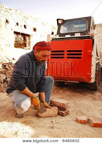Man Scraping Bricks In Front Of Bobcat Skid Loader