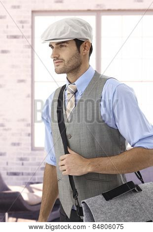 Stylish young caucasian businessman in cap leaving office, looking away, smiling.