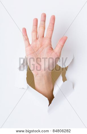 Hand palm breaking through paper wall