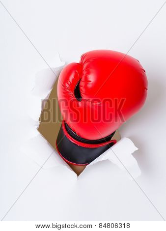 Boxing glove through a hole in paper