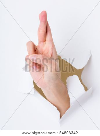 Lucky sign hand gesture breaking through the paper wall
