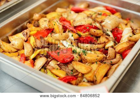 Steel container with roasted potato wedges and vegetables