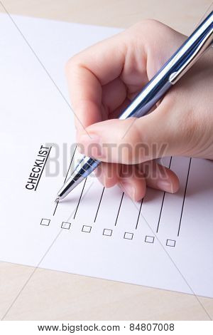 Female Hand Filling Checklist With Pen