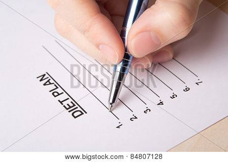 Female Hand Filling Her Diet Plan With Pen