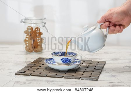 Pouring a cup of tea with cookie jar of gingerbread in the background