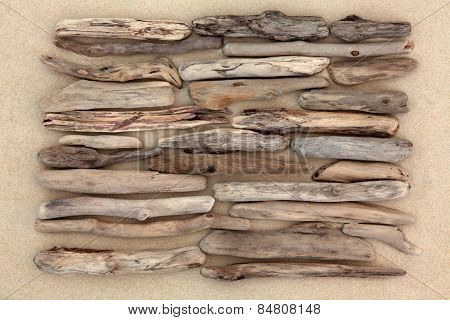 Driftwood abstract design on beach sand background.