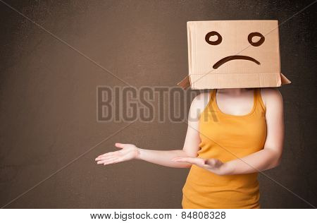 Young girl standing and gesturing with brown cardboard box on her head with sad face