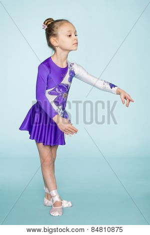 Wonderful cute girl seven years dancing on a blue background.