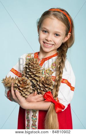 Beautiful girl in a traditional Russian folk costume holding pine cones. Girl seven years.
