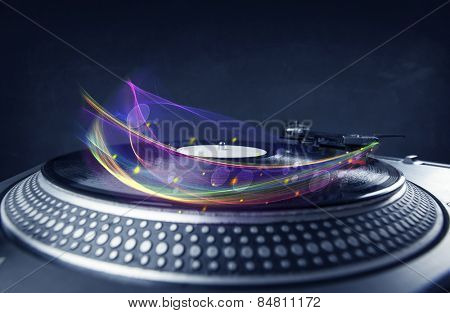 Turntable playing vinyl with glowing abstract lines concept on background