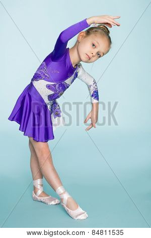 Wonderful sweet girl seven years dancing on a blue background.