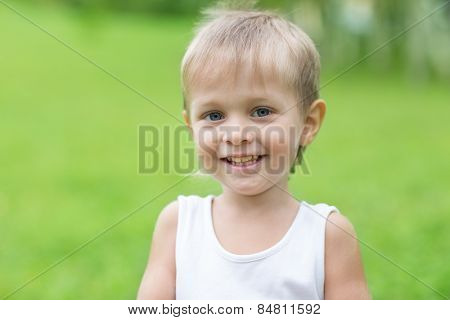 Cheerful boy on a background of green. Boy three years.