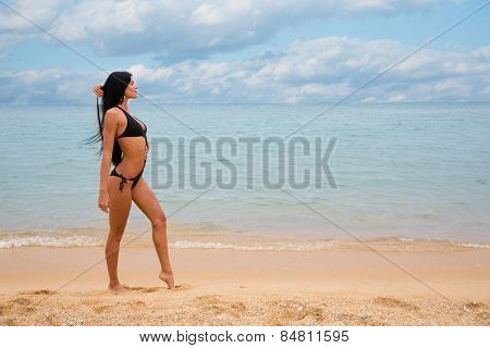 Beautiful sexy girl with black hair in a bathing suit on the beach.