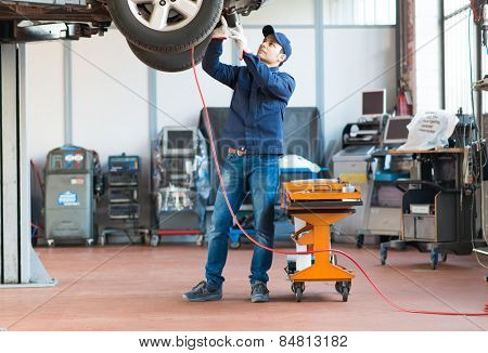 Mechanic screwing a tyre with a pneumatic wrench