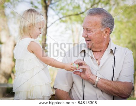 Cute Baby Girl Handing Easter Egg to Grandfather Outside at the Park.