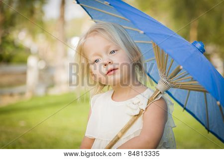 Playful Cute Baby Girl Holding Parasol Outside At The Park.