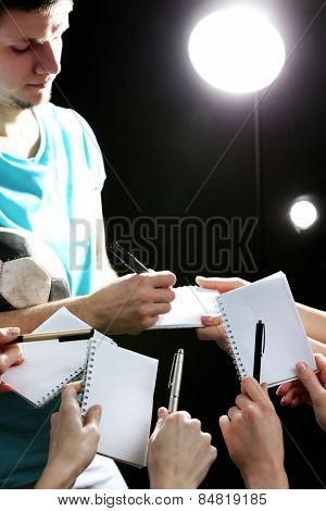 Autographs by football star on black and lights background