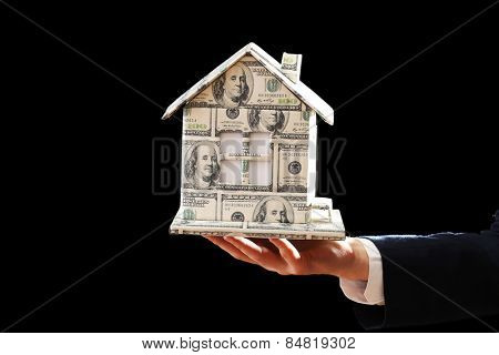 Model of house made of money in male hand on dark background