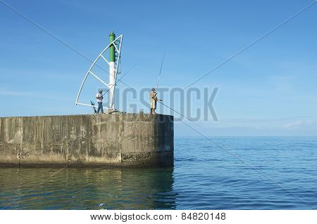Men do fishing from the pier in Ravine Saint-Gilles De Reunion, France.