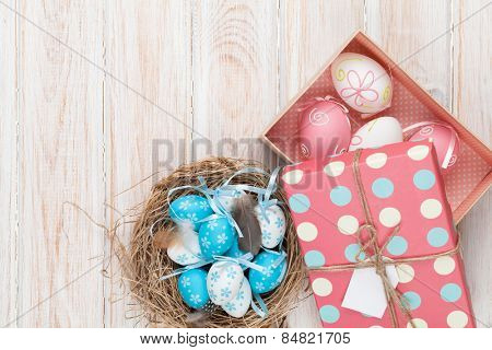 Easter with blue and white eggs in nest and gift box over white wood. Top view with copy space