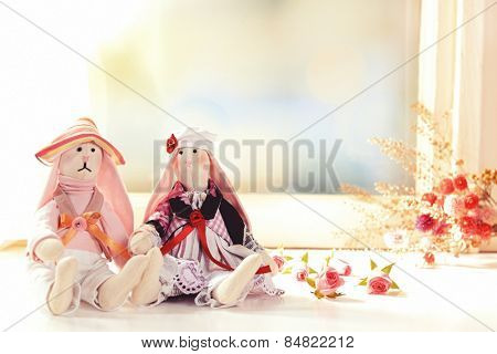 Handmade dolls near window close-up