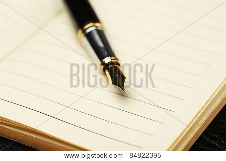 Writing pen on notebook background