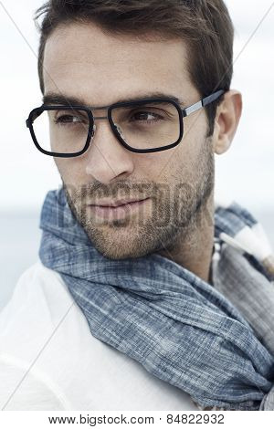 Mid adult man wearing scarf and spectacles on beach