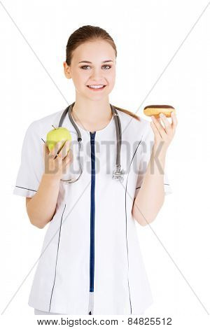 Happy nutritionist holding a donut and apple