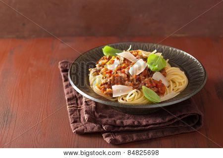 italian pasta spaghetti bolognese with basil on rustic table