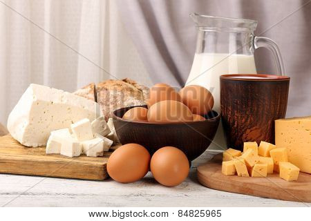 Tasty dairy products with bread on table on fabric background