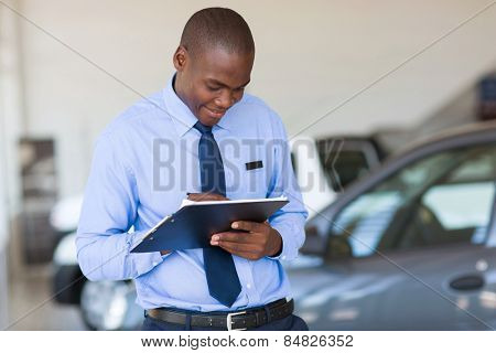 successful african american man working at vehicle showroom
