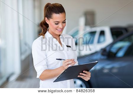 pretty saleswoman working at car dealership