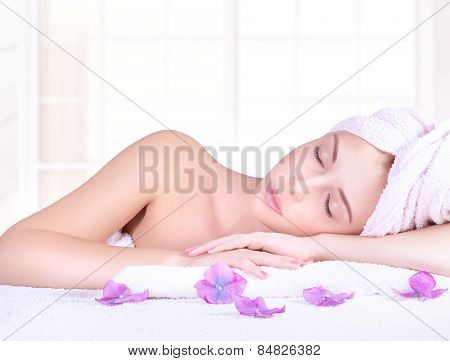 Beautiful woman with closed eyes lying down on massage table, enjoying day spa, luxury beauty salon, healthy lifestyle