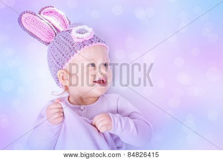 Portrait of cute Easter bunny over blur background, sweet little baby wearing purple hat with rabbit ears, celebrating religious holiday