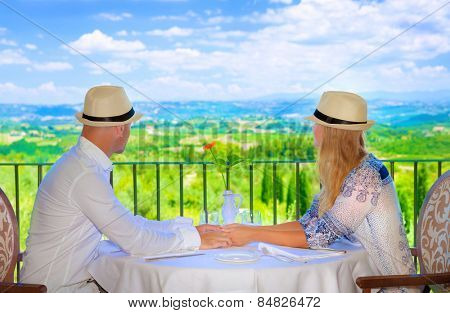 Happy couple on resort, side view of young family sitting on restaurant terrace and having lunch, enjoying beautiful landscape, love and romance concept