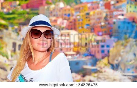 Attractive girl enjoying travel to Europe, standing on wonderful colorful buildings background, famous town in Cinque Terre, Italy