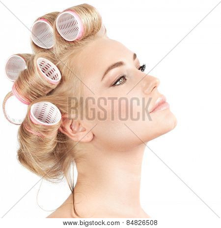 Closeup portrait of beautiful blond woman with curlers on hair isolated on white background, making hairdo, luxury beauty salon