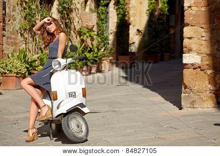 beautiful italian woman sitting on a italian scooter.