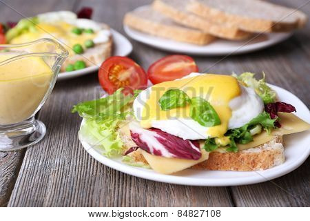 Toast with egg Benedict and tomato on plate on wooden table