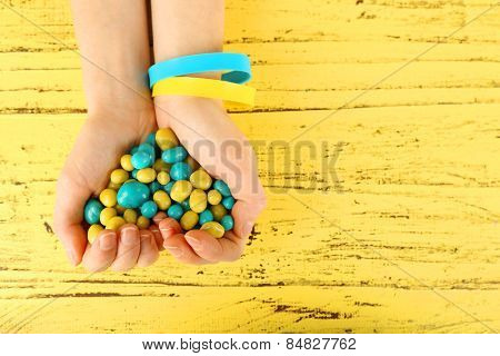 Hands with blue-yellow candies - colors of flag of Ukraine, on wooden background
