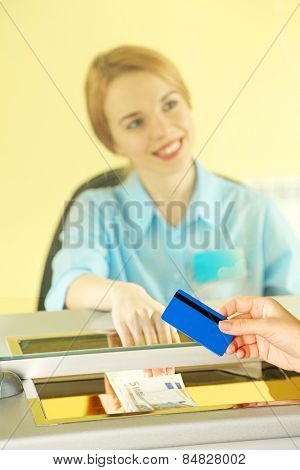 Female hand with credit card in cash department window