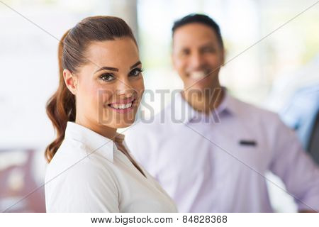 attractive vehicle sales woman standing in front of colleague