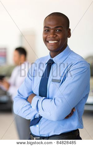 portrait of african vehicle salesman in showroom