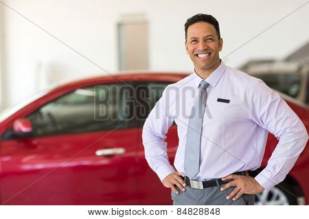 middle aged vehicle sales consultant inside showroom