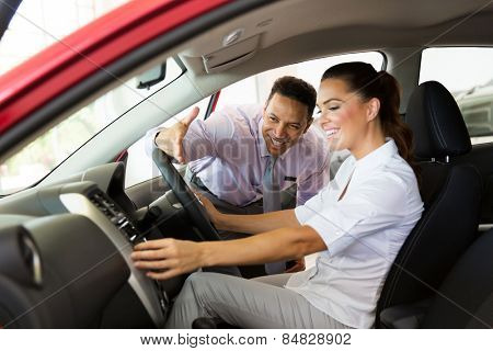 friendly car sales consultant showing a new car to young woman