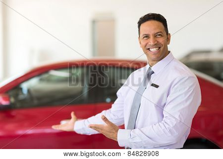 handsome vehicle salesman presenting new cars in showroom