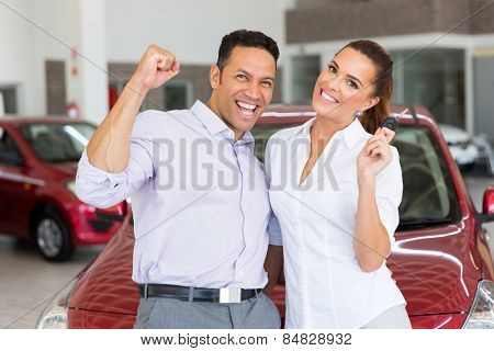 excited couple just bought a new car from dealership