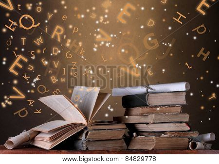 Old books with flying letters on table on dark background