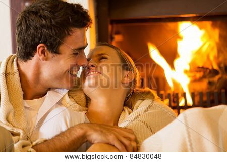 romantic young couple cuddling on couch